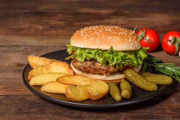 맛있는 구운 수제 버거. 맛있는 구운 햄버거. 나무 테이블에 공예 쇠고기 햄버거와 감자 튀김