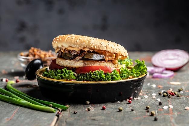 木製のテーブルにチキン、ピクルス、揚げタマネギを添えたおいしい自家製ハンバーガーのグリル。バナー、メニュー、テキストのレシピの場所