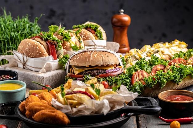 素朴な木製の背景に牛肉、トマト、チーズ、ベーコン、レタスを添えたおいしい自家製ハンバーガーのグリル。ファーストフードとジャンクフードのコンセプト
