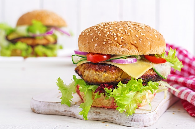 Tasty grilled homemade hamburger with burger chicken, tomato, cheese, cucumber, lettuce and beetroot.