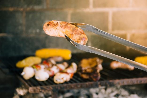 Tasty grilled sausage in metal tongs