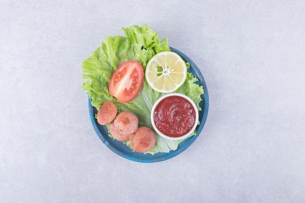Gustose salsicce alla griglia e ketchup sul piatto blu.
