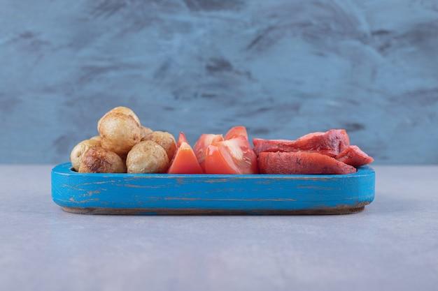 Salsicce e pomodori arrostiti saporiti sul piatto blu.