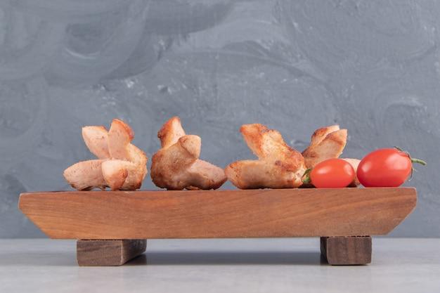 Gustose salsicce alla griglia con pomodori su tavola di legno.