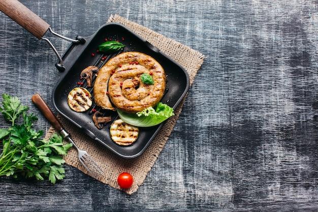 Вкусные спиральные колбаски гриль для еды на сером фоне деревянных