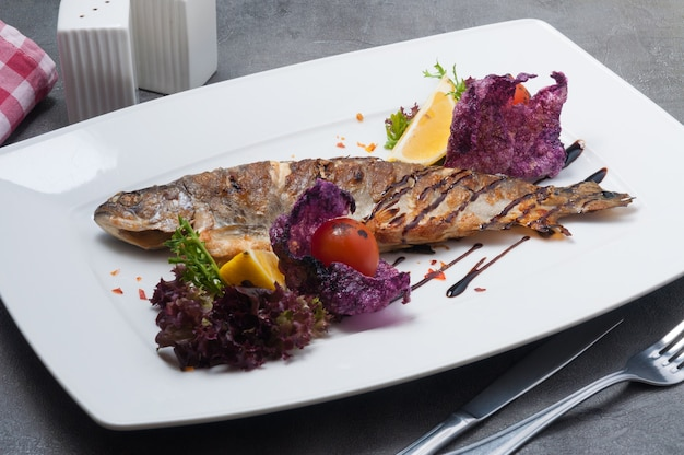 Tasty grilled trout with lemon tomatoes and lettuce