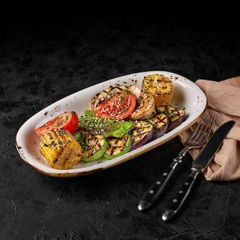 暗い背景の鍋においしい焼き野菜。健康食品、夏の食品のコンセプト。