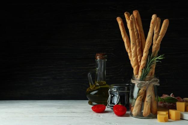 Вкусные палочки гриссини и закуски на деревянном фоне