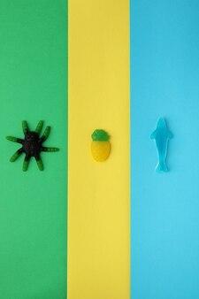 Tasty gummy candies on three tone background.