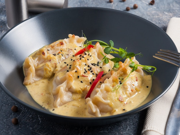 Tasty gyoza dumplings in curry sauce decorated with micro greenery in a dark plate