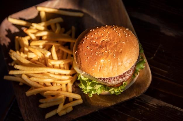 Tasty hamburger and fried potatoes