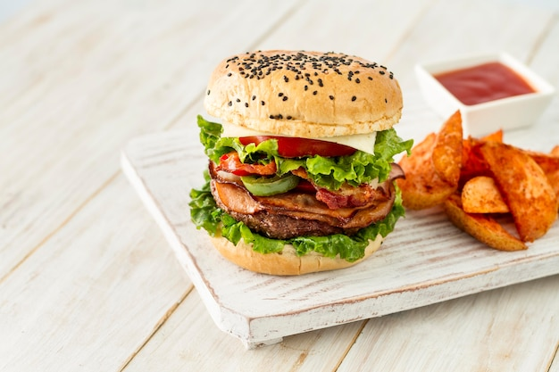 Tasty hamburger with fries on wooden board