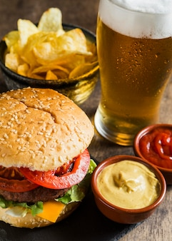 Tasty hamburger with glass of beer and chips