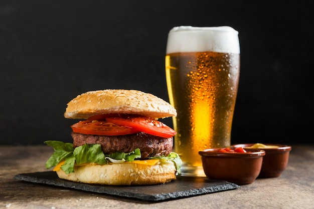 Tasty hamburger with glass of beer and ketchup sauce