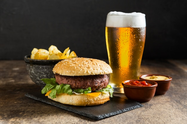 Tasty hamburger with glass of beer and sauces