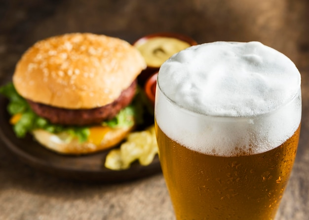 Tasty hamburger with glass of foamy beer