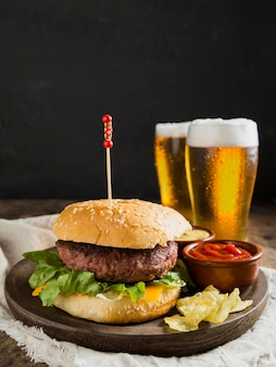 Tasty hamburger with glasses of beer and chips