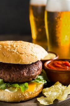Tasty hamburger with glasses of beer and ketchup