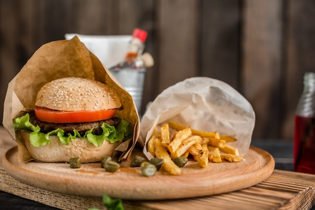 Tasty hamburger with meat and vegetables against a dark background. fast food. it can be used as a background