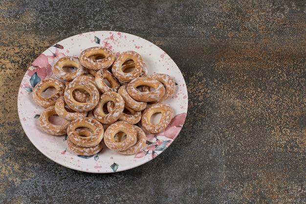 Вкусные крекеры с солью на красочной тарелке.