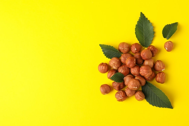 Tasty hazelnuts and leaves on yellow background. vitamin food