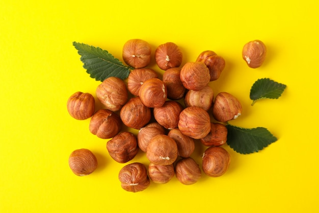 Tasty hazelnuts and leaves on yellow.
