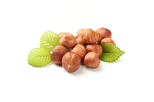 Tasty hazelnuts with leaves isolated on white background