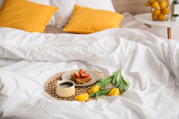 おいしい健康的な朝食とベッドの上の花