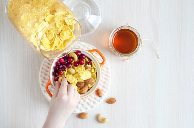 Tasty and healthy breakfast. corn flakes topped with berries, nuts, honey. children's hand and food.