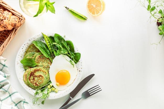 おいしい健康的な朝食。ほうれん草、卵、若いグリーンピースのグリーンパンケーキ。上面図。コピースペース。
