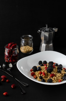Tasty healthy breakfast. oatmeal porridge with wild berries on dark background.
