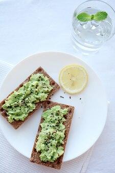 Вкусный здоровый тост на завтрак с авокадо и стаканом чистой воды