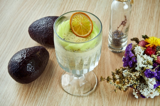 Tasty and healthy dessert pudding with chia and passion fruit in a beautiful glass on a wooden table