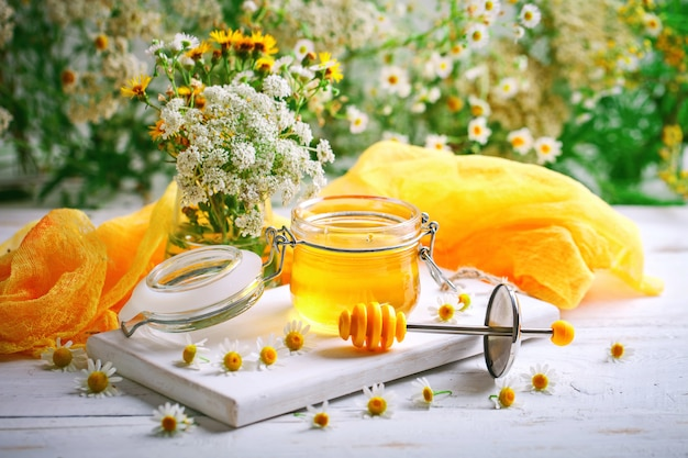 Tasty and healthy honey on white wooden table with flowers of chamomile.