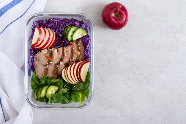 Tasty healthy lunch of vegetables and baked turkey. salad of red cabbage, spinach, apples, fresh cucumbers with diet meat in a glass lunchbox. background