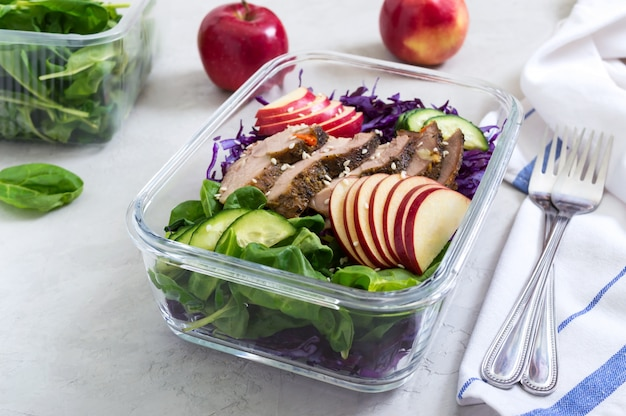 Tasty healthy lunch of vegetables and baked turkey. salad of red cabbage, spinach, apples, fresh cucumbers with diet meat in a glass lunchbox. sports diet. proper nutrition.