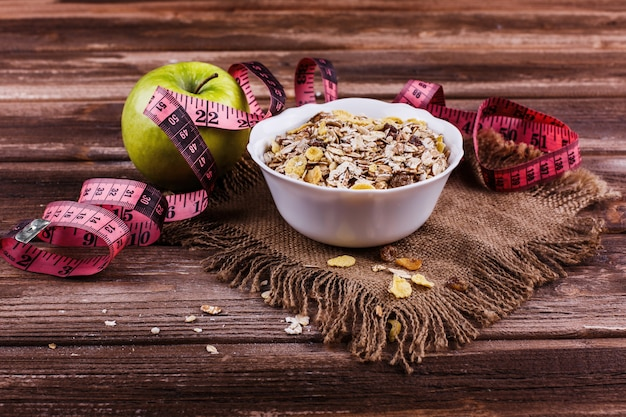 Tasty healthy morning breakfast made of milk and porridge with nuts, apples and bananas