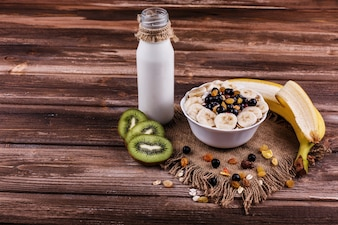 Tasty healthy morning breakfast made of milk and porridge with nuts, kiwis and honey