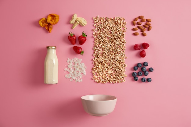 Tasty healthy natural ingredients for breakfast on pink background. fresh milk in bottle, bowl, flakes, raw raspberry, blueberry, strawberry, almond, dried apple, apricot. cooking delicious oatmeal