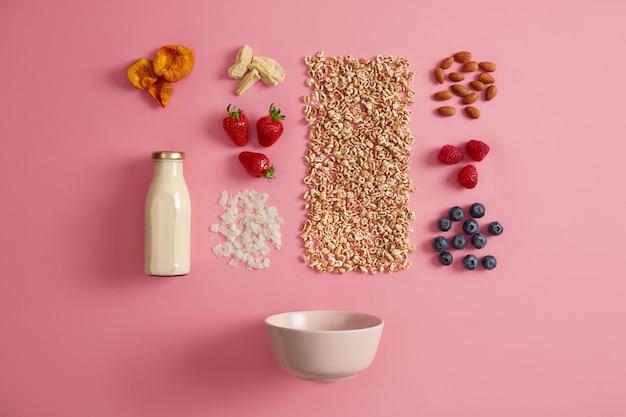 ピンクの背景に朝食のためのおいしい健康的な天然成分。ボトル、ボウル、フレーク、生のラズベリー、ブルーベリー、イチゴ、アーモンド、乾燥リンゴ、アプリコットの新鮮な牛乳。おいしいオートミールを調理する
