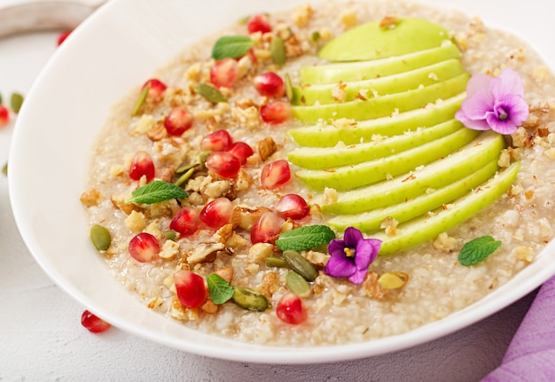 Tasty and healthy oatmeal porridge with apples, pomegranate and nuts. healthy breakfast. fitness food. proper nutrition
