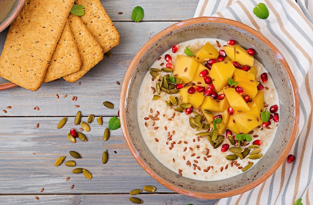 Tasty and healthy oatmeal porridge with mango, pomegranate and seeds. healthy breakfast. fitness food. proper nutrition. top view