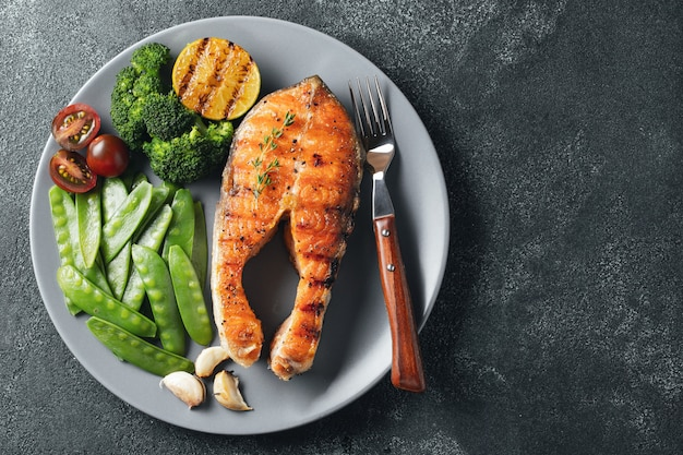 Tasty and healthy salmon steak with green peas, broccoli and tomatoes on a gray plate.