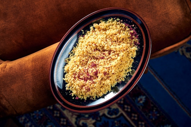 A tasty and healthy side dish for the main course - couscous porridge with oriental spices served in a black plate. top view