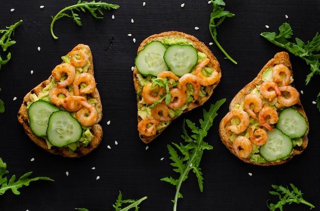 Вкусная полезная закуска с тостами из авокадо, огурцом и креветками. плоская планировка, вид сверху.