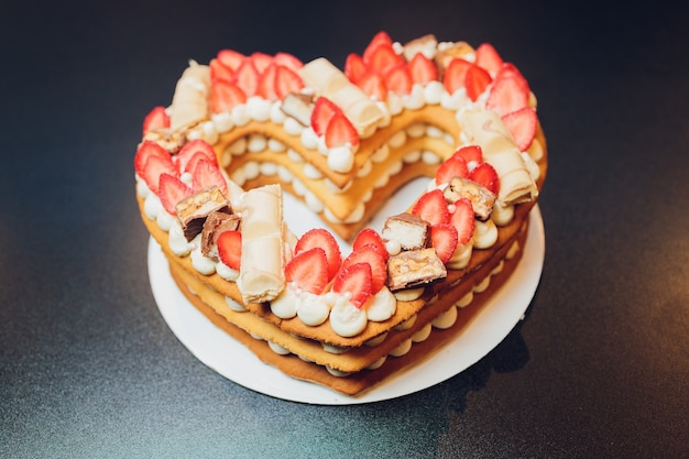 Tasty heart-shaped cake with fresh berries on a black background.