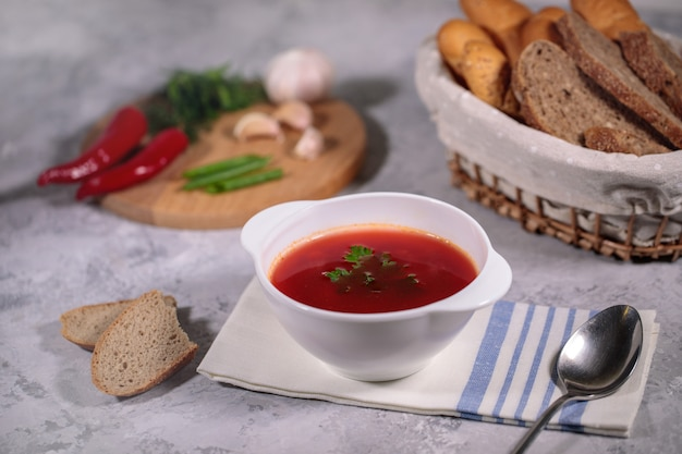 Tasty and hearty dinner. a plate with borsch on the table, next to the board is parsley, dill, green onions, garlic, chili pepper and a basket with bread.