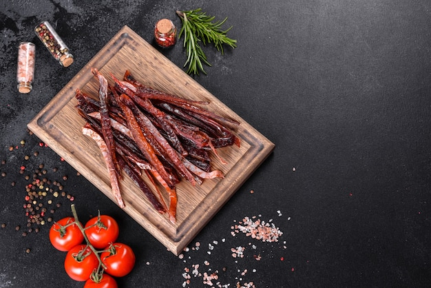 Tasty hearty meat salted and dried with pieces of spices and herbs. fast and hearty snack