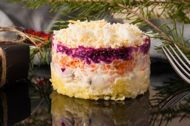 Вкусный салат из сельди под шубой на черном фоне крупным планом