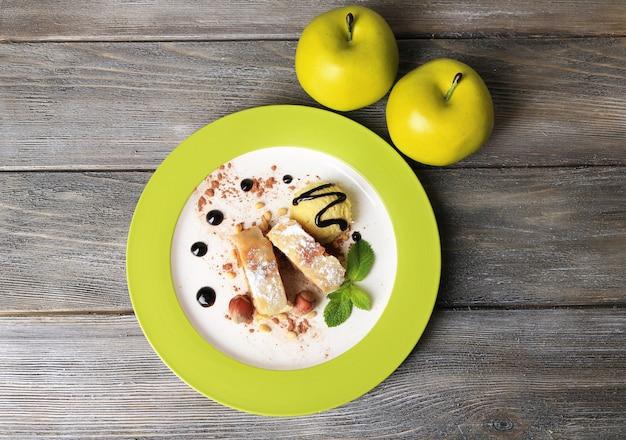 木製の背景に、ナッツ、ミントの葉、プレートにアイスクリームを添えたおいしい自家製アップルシュトルーデル